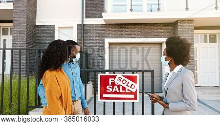 African American Young Happy Couple In Medical Masks Buying House At Outskirt And Talking With Femal