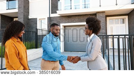 Female Real-estate Selling House To African American Happy Couple And Passing Keys. Outdoors. Cheerf