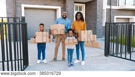 Portrait Happy African American Family With Small Children Standing At New House At Suburb And Smili