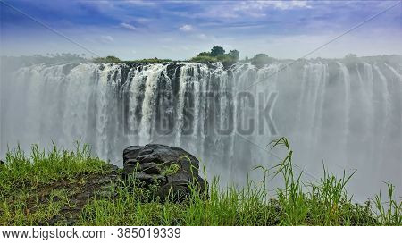 Victoria Falls, Zimbabwe. Powerful Streams Of The River Fall Into The Abyss. There Is A Mist Of Wate