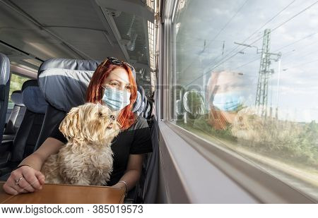 Young Redhead Woman And Dog Traveling By Train, During Pandemic. Millennial Girl With A Medical Mask