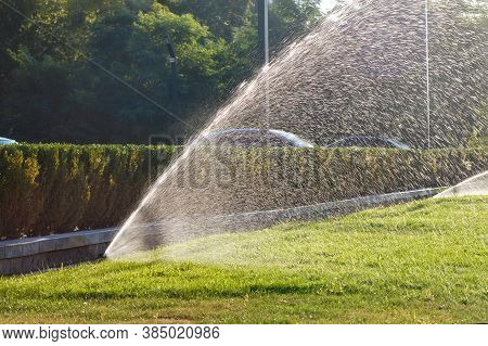 Beautiful Spray Of Water In The Backlight Of The Evening Sun Created By A Powerful Sprinkler System
