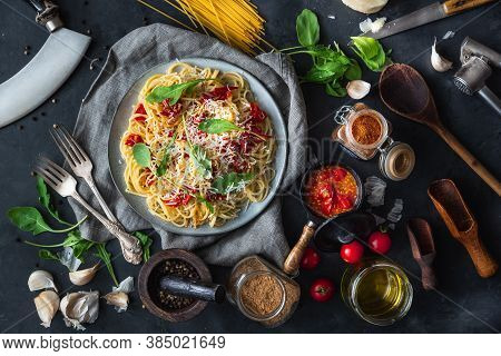 Italian Dinner With Pasta On Ceramic Plate With Ingredients Around On Black Background. Flat View. T