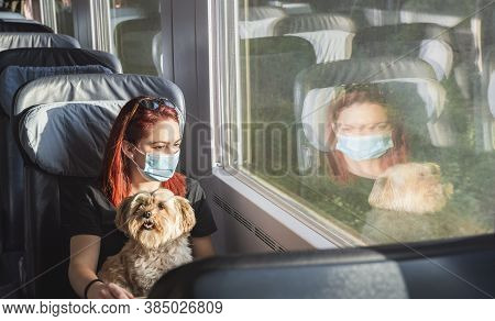 Young Redheaded Woman With Face Mask Traveling By Train, At First-class. Girl And Dog Travel By Germ