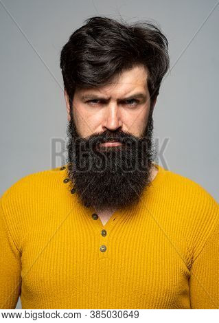 Portrait Of Handsome Serious Man With Beard And Mustache, Looks Seriously, Isolated On Grey Wall