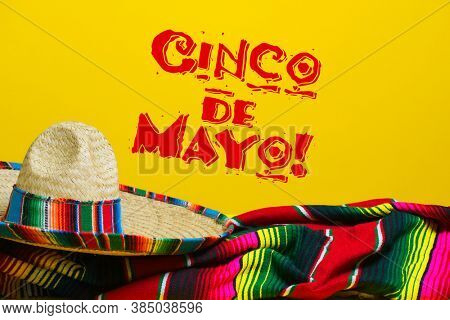 Mexican Serape blanket and sombrero on yellow background with Cinco de Mayo.