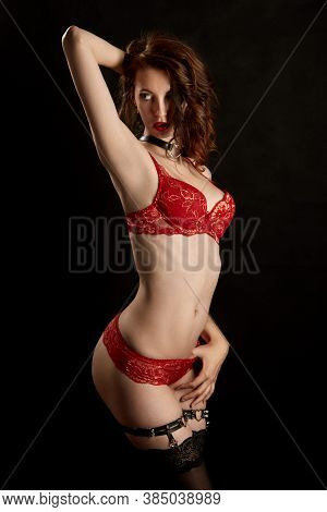 Beautiful Slim Woman In Red Lingerie Show Strip Tease On Black Background