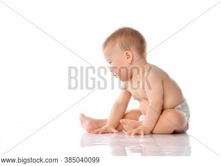 Cute Little Baby In A Diaper Clapping His Hands While Sitting On The Floor. Excited Toddler Child Wi