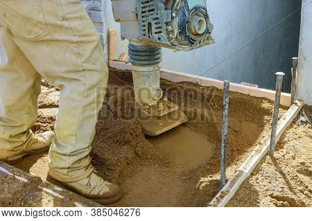 Worker Uses Compactor To Vibratory Power Tool At Soil At Worksite Construction New Sidewalk