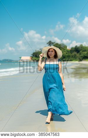 Asian Woman In Blue Dress In Summer On The Sand On The Beach Of Tropical Island.