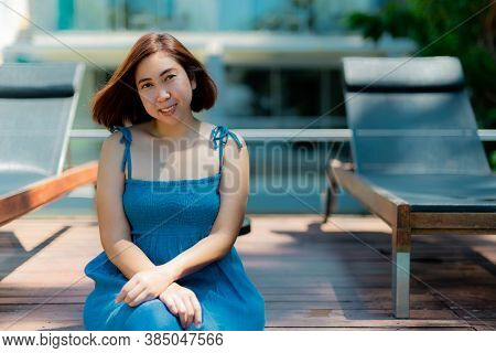 Asian Woman In Blue Dress In Summer On The The Swimming Pool Of Tropical Island.