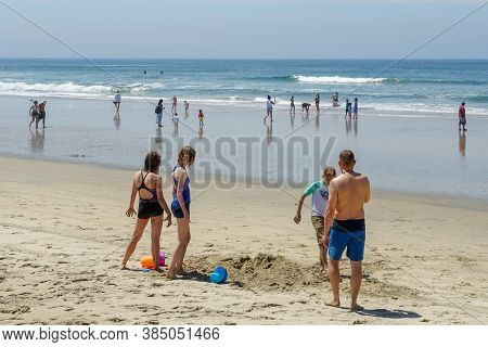 Families Playing And Building Sand Castle At The Beach During Beautiful Summer Day At Huntington Bea