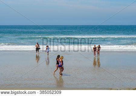 Tourist And Families On The Beach Enjoying Beautiful Summer Day At Huntington Beach, California. Usa