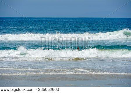 Young Kid At The Beach Enjoying The Waves And Beautiful Summer Day At Huntington Beach, California.