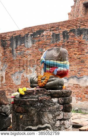 There Is No Head, Incomplete Of Ancient Stone Buddha And Worship By Colorful Fabric And Flower In Th