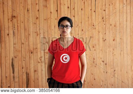 Woman Wearing Tunisia Flag Color Shirt And Standing With Two Hands In Pant Pockets On The Wooden Wal