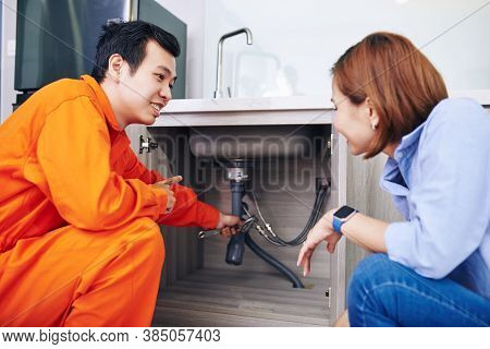 Smiling Vietnamese Plumber Showing Fixed Or Installed Pipes Under Sink In Kitchen Of Young Woman