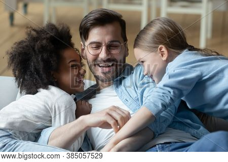 Playful Small Little Mixed Race Daughters Tickling Laughing Young Father.