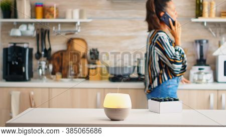 Woman Talking On The Phone With Essential Oils Aromatherapy Next To Her In The Kitchen. Aroma Health