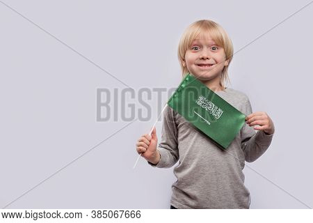 Surprised Blond Boy Holding Flag Of Saudi Arabia. Travel To Saudi Arabia With Children.