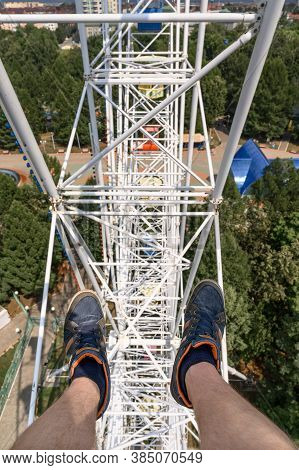 From Above Anonymous Man In Sneakers Riding Modern Ferris Wheel Over Green Trees On Fairground In Su
