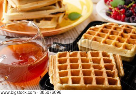 Belgian Waffles On Cast Skillet With Stacked Ones And Syrup Jug  Aside
