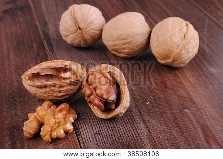 whole and cracked walnuts on a wooden table