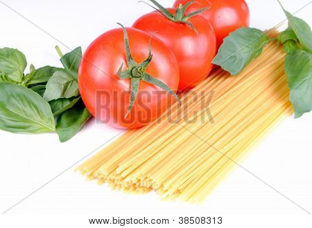 raw spaghetti tomatoes and basil on white soft shadows