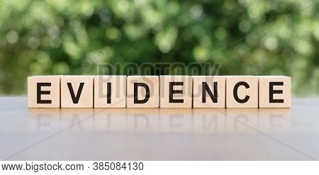 Evidence Word Written On Wooden Blocks. The Text Is Written In Black Letters And Is Reflected In The