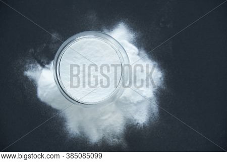 Glass Bowl Of Baking Soda. Spoonful Of Bicarbonate. Top View, Flat Lay. Close Up On A Black Backgrou
