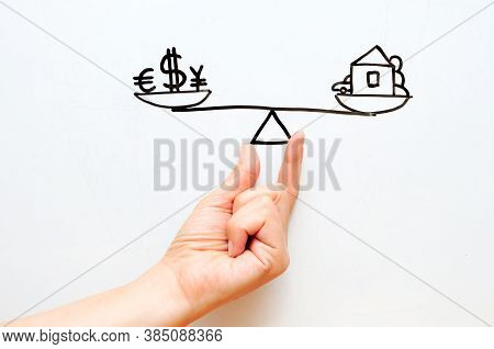 Hand With Scales. A Bowl With Finance Against A Bowl With Property