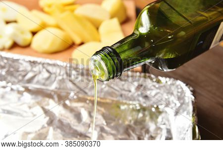 Cooking, Baking Potatoes. Pouring Olive Oil From Green Bottle Into Baking Pan