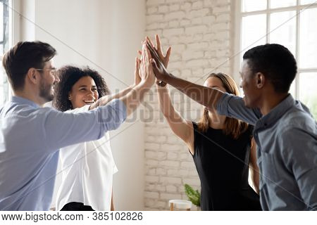Excited Multiethnic Coworkers Give High Five Engaged In Teambuilding Activity