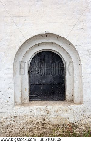 Arched Window Closed With Black Iron Shutters On A Old White Stucco Wall Of The Monastery. Close-up