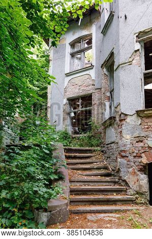 Exterior With Stairs Of An Old Abandoned Mansion Overgrown With Greenery