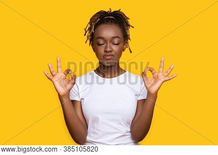 Peaceful African Woman Staying Calm, Meditating On Yellow Studio Background
