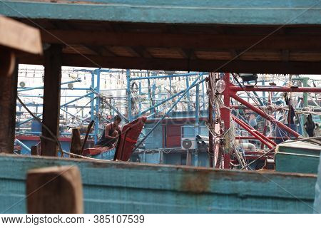 Jakarta, Indonesia May 6, 2019: Photos Through A Fishing Boat Saw Fisherman Tying Red Cloth At Prow