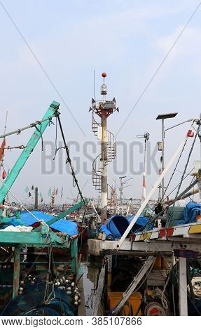 Pole Tower For Signal Light Among Many Indonesia Fishing Boats Moored In The Port Harbor.
