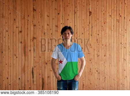Man Wearing Djibouti Flag Color Shirt And Standing With Two Hands In Pant Pockets On The Wooden Wall
