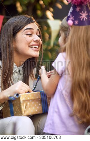 beautiful young adult brunette with  pleased face unwrapping birthday present for little caucasian girl
