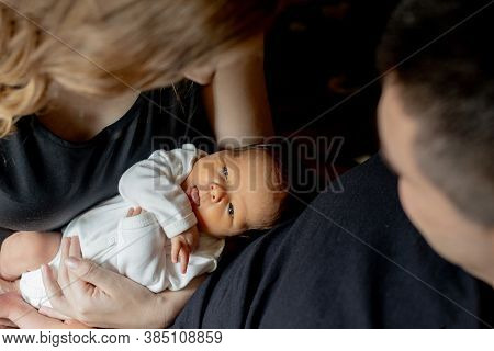 Young Father And Mother Holding Their Newborn Baby Son. Mom, Dad And Baby. Happy Family Concept. Cop