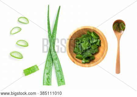 Isolated Of Top View Green Fresh Aloe Vera Leaf Are Sliced In Wooden Bowl And Spoon On White Backgro