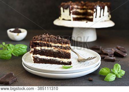 Slice Of Chocolate Cake. Chocolate Truffle Cake With Cream Cheese On A Dark Background.