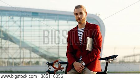 Portrait Of Handsome Stylish Young Man In Red Jacket Looking At Camera, Holding Newspaper Under Arm