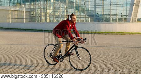 Caucasian Young Stylish Male Bicyclist In Red Casual Jacket And Headphones Riding A Bike At Street I