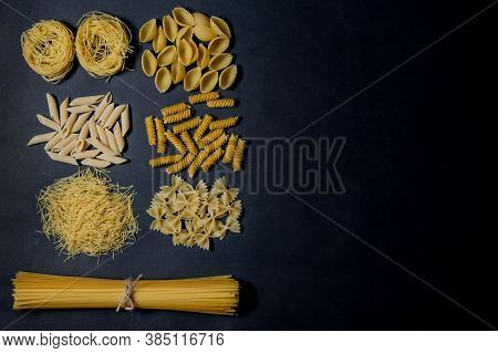 Assorted Types Of Pasta On Black Background. Top View. Various Forms Of Pasta. Copy Space For Design