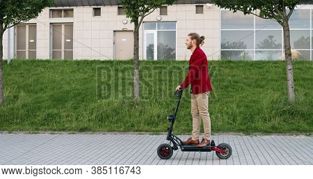 Caucasian Cheerful Stylish Young Man In Red Jacket Riding Electric Scooter And Standing Still On Str