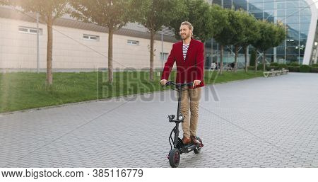 Caucasian Cheerful Happy Stylish Young Man In Red Jacket Riding Electric Scooter And Standing Still