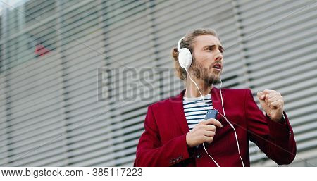 Caucasian Young Stylish Handsome Man In Headphones Listening To Music On Smartphone And Singing. Out