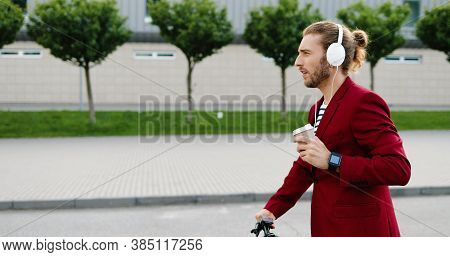 Caucasian Young Stylish Handsome Man In Headphones Driving Electric Scooter At Street, Listening To